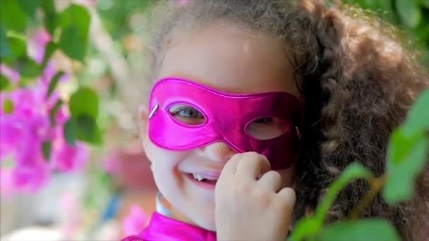 Bella ragazza Llittle nel costume da supereroe, vestita con un mantello rosa e la maschera delleroe. Gioca sullo sfondo del mare e il cielo blu e nuvole, corregge la maschera rosa sul suo volto