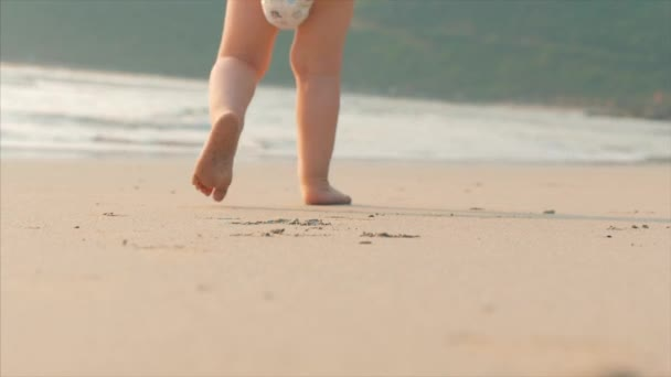 Silhouette of childrens Feet walking on wet sand in along a tropical beach on a tropical ocean background. Concept: Children, Happy Childhood, Summer, Child, Vacation. Soft focus.