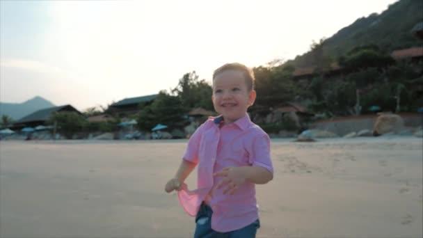 Boldog gyerek fut végig a parton. Sziluettje gyermek láb Walking on nedves homok mentén egy trópusi tengerparton egy trópusi óceáni háttérben. Koncepció: gyerekek, boldog gyermekkor, nyár, Child. Soft fókusz
