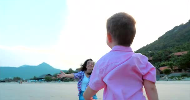 Close-up of mother hugs and kisses son, son runs into mothers arms, hugs mother. Happy child rushes into hands of mother. Family hugs over sunset sky background. Stock Footage.
