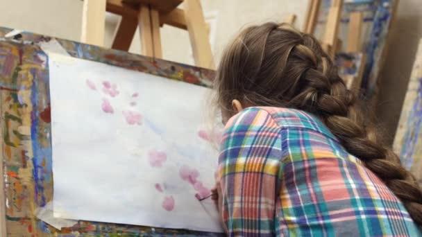 Kis lány művész felhívja a festőállvány. Rajz folyamat: közeli, ecset és vászon.