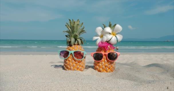Na tropické pláži blízko horké letní slunce na pobřeží tropického exotického moře, které stojí na písečném tropickém ovoci. Koncept letní pozadí.