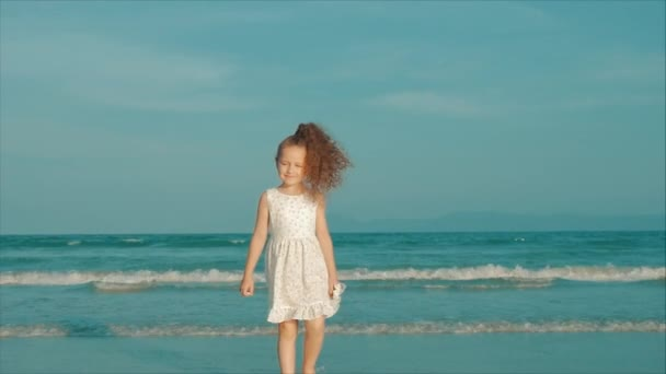 Göndör kislány, fehér ruhában sétált a tengerparton naplementekor. Lassított. Boldog gyermekkor, szabadság és utazás koncepció.