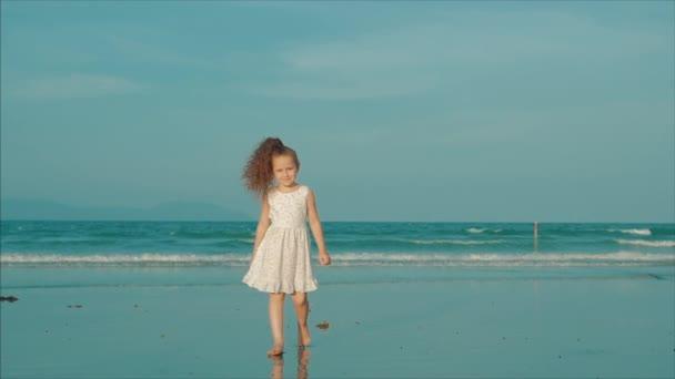 Malá kudrnatá holčička v bílých šatech na pláži při západu slunce. Zpomaleně. Šťastné dětství, koncepce svobody a cestování.