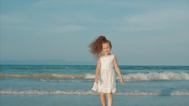 Curly little girl in white dress walking on the beach at sunset. Slow Motion. Happy Childhood, Freedom and Travel concept.
