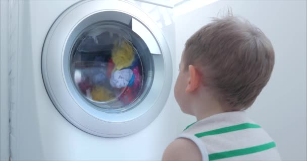 Cute Child Looks Inside the Washing Machine. Cylinder Spinning Machine. Concept Laundry Washing Machine, Industry Laundry Service.