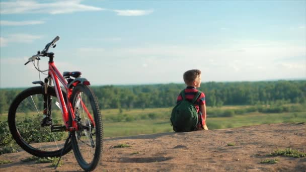 Teenager in a Red T-Shirt With a Backpack on his Back, at Sunset, Sitting on a High hill, Enjoying Nature, Freedom, Against the Background of his Bike.