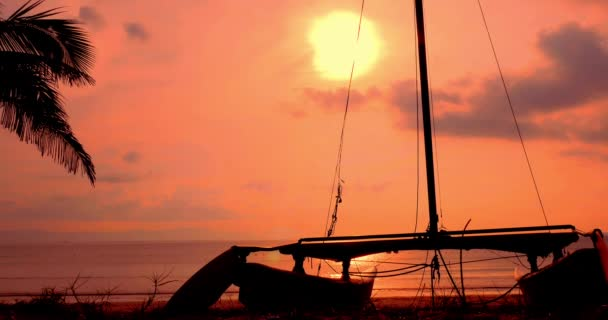 Beautiful Sunset in the Tropics on the Backdrop of the Ailboat on the Sand and Ocean. Concept Nature, Vacation, Relaxe. Soft Focus.