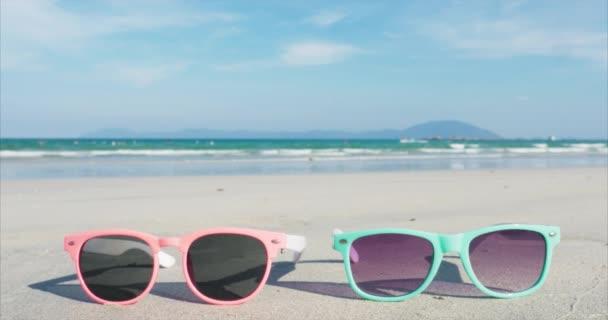 Blízká Tropická Pláž sluneční brýle růžová a modrá leží na bílém písku proti oceánu.