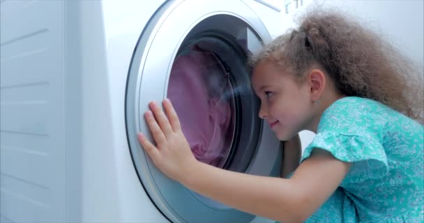 Close Up Cute Child Looks Inside the Washing Machine. Cylinder Spinning Machine. Concept Laundry Washing Machine, Industry Laundry Service.