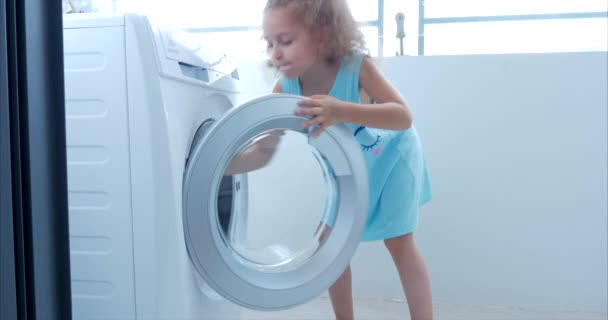 Little Girl Loads the Laundry in the Washing Machine and includes washing. Concept Laundry Washing Machine, Industry Laundry Service.