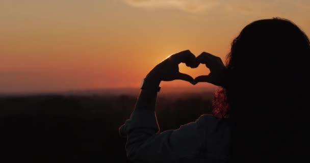 Krásná žena, takže tvar srdce s rukama na západu slunce dívku zvedl lásku symbolem gesto s oranžové sluneční erupce.