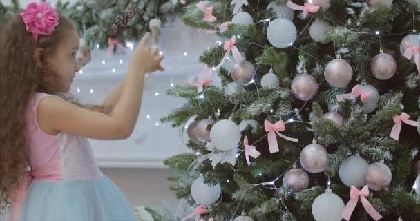 Cu kislány ünnepi ruhában, göndör haja lógott a karácsonyfa, karácsonyi fények, karácsonyi díszek. A labdát a karácsonyfa dekoráció. 4k