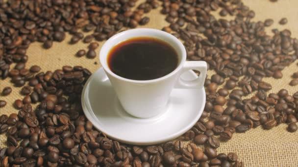 Kávéscsésze és szemes kávé. Fehér csésze párologó kávé az asztalra, sült bab. Stock-felvételek.