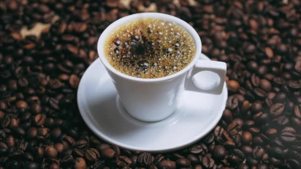 Coffee cup and coffee beans. White cup of evaporating coffee on the table with roasted bean. Stock footage.