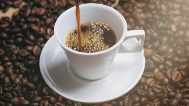 Šálek kávy a kávové fazole. Bílý šálek odpařující kávy na stole s opečenou fazolí. Skladní záznam.