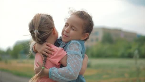 Két mosolygó, göndör, aranyos nővérek Baby-Girls ölelés szorosan egymást. Boldog gyermekkor, pozitív érzelmek, igaz érzések.