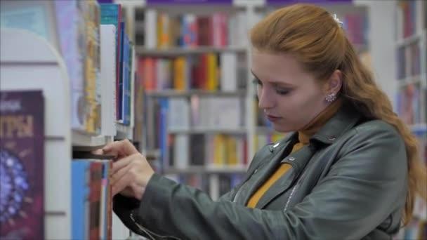 Portrét mladé krásné ženy s jasně červenými vlasy v brýlích, hezká dívka čtení v knihovně University.