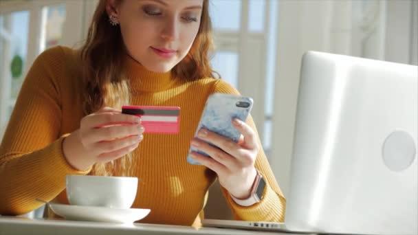 an einem sonnigen Tag. schöne sonnige Tag junge Frau trinkt Morgenkaffee in einem Café, so dass ein Online-Kauf einfach Zahlung im Internet mit einem Handy oder Laptop.