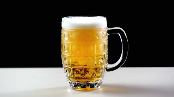 Pivo se nalije do sklenice na černém pozadí. Pěna rychle snímky přes sklo. Extrémní velké pivní pěny a bublin. Plný hrnek tmavého piva na černém pozadí. Zpomalený pohyb.