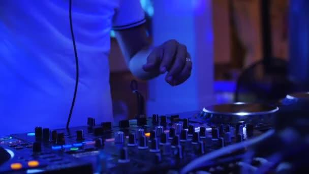 DJ kezek Close up DJ hangvezérlő panel keverésére tánczene fényes villanások színes show diszkó klubban.Kezek érintse csúszkák, játszani elektronikus zenét mixer, színes megvilágítás nightclub, tánc