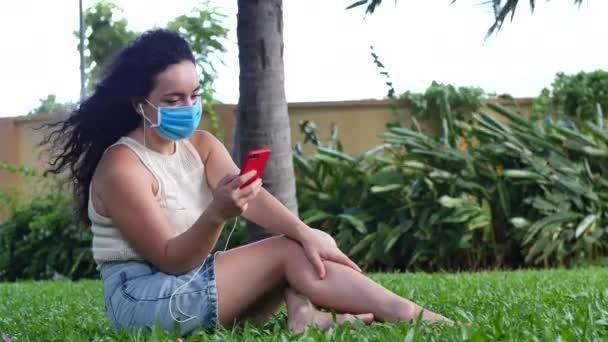 Žena v masce před epidemií koronaviru sedí v samotě v parku, používá telefon Poslouchat hudbu přes sluchátka, typy na smartphonu textové zprávy, koncepce lidí na self-izolaci od globální epidemie