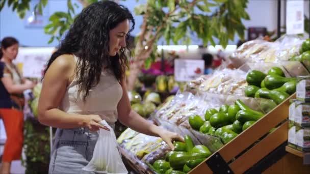 Hübsche junge Frau oder Mutter kauft im Supermarkt ein, wählt Produkte im Supermarkt zum Kochen, gesunde Lebensmittel, Tomaten, Avocados, Früchte, Orangen auf dem Markt, Supermarkt.
