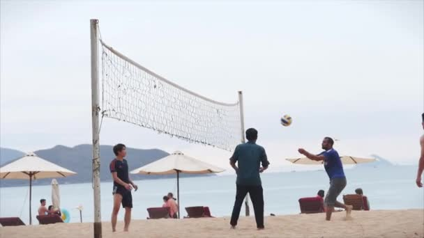 Po izolační karanténě. Covid-19. Přátelé hrají plážový volejbal při západu slunce, volejbalový štít ve filmu Nha Trang, Vietnam, 14. května 2020.