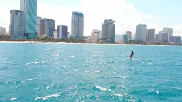 Kitesurfing place, sports concept, healthy lifestyle, human flight. Aerial view of the city beach and active people practicing kite surfing and windsurfing.