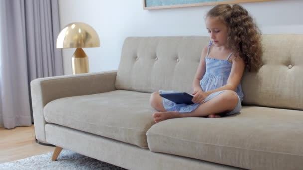 Roztomilé holčička předškolní dítě pomocí digitálního tabletu technologie zařízení vypadá telefon.Hraje v telefonu sedí na pohovce.Děti tech závislost koncept hrát hru doma.