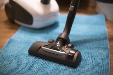 Vacuum cleaner on light blue carpet.