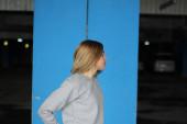 Girl  blonde  in grey hoodie. Street style. Advertising brand cl