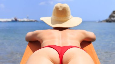 Back view of woman in hat lying on the deckchair and relaxing on beach. Big butt closeup.