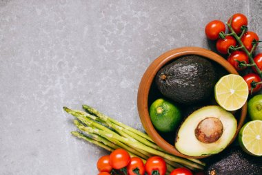 Fresh healthy vegetables in wooden plate on gray background