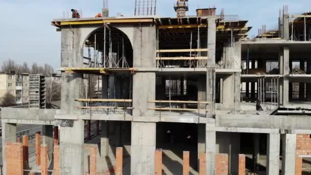Letecký snímek budovy v procesu výstavby. Práce v velké staveniště. V pozadí pracuje jeřáb a město. Střílel na 4k Uhd fotoaparát
