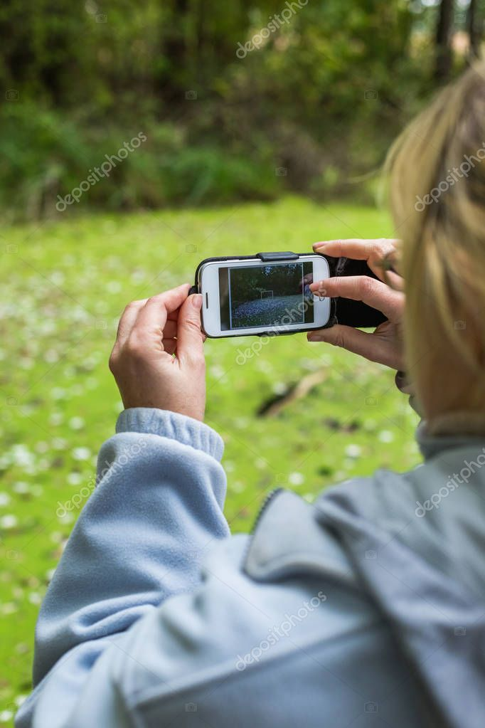 A blonde woman using a phone takes a photo of a beautiful landscape.