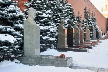 MOSCOW, RUSSIA - Jan 25, 2018 The line of tombs of Soviet leaders (Stalin's tomb in foreground) and blue pine trees covered snow in winter along the wall of Moscow Kremlin at the necropolis at Red Square. necropolis at the Red Square.