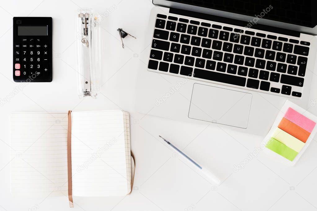 directly above shot of white desk with notebook, calculator, note pad and office supplies