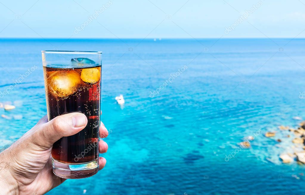 hand holding drinking glass with ice-cooled cola against blue sky and sea