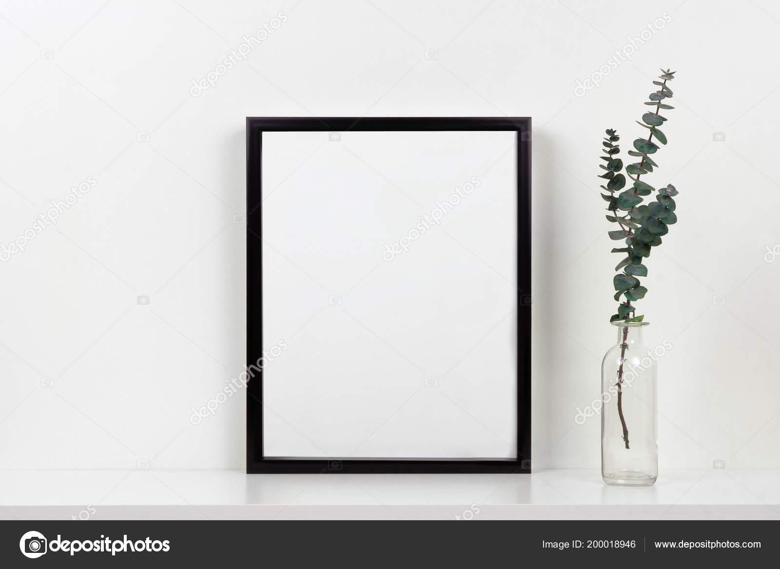 Maquette cadre noir avec vase branches sur une Étagère bureau