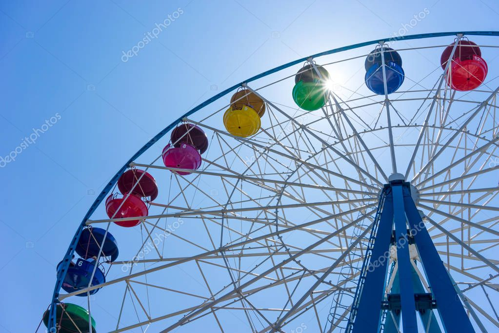 Ferris wheel with colored cabins on background of blue sky