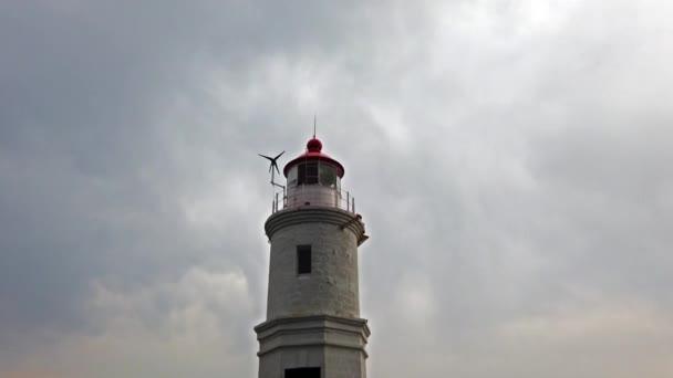 Landschaft mit weißem Leuchtturm vor bewölktem Himmel.