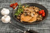 Fotografie Stewed pork chop in a bright mushroom sauce.