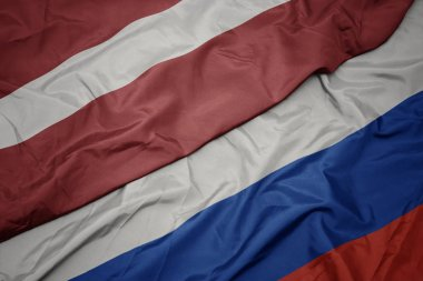 waving colorful flag of russia and national flag of latvia.