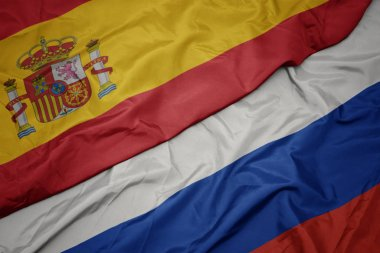 waving colorful flag of russia and national flag of spain.