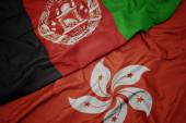 waving colorful flag of hong kong and national flag of afghanistan. macro