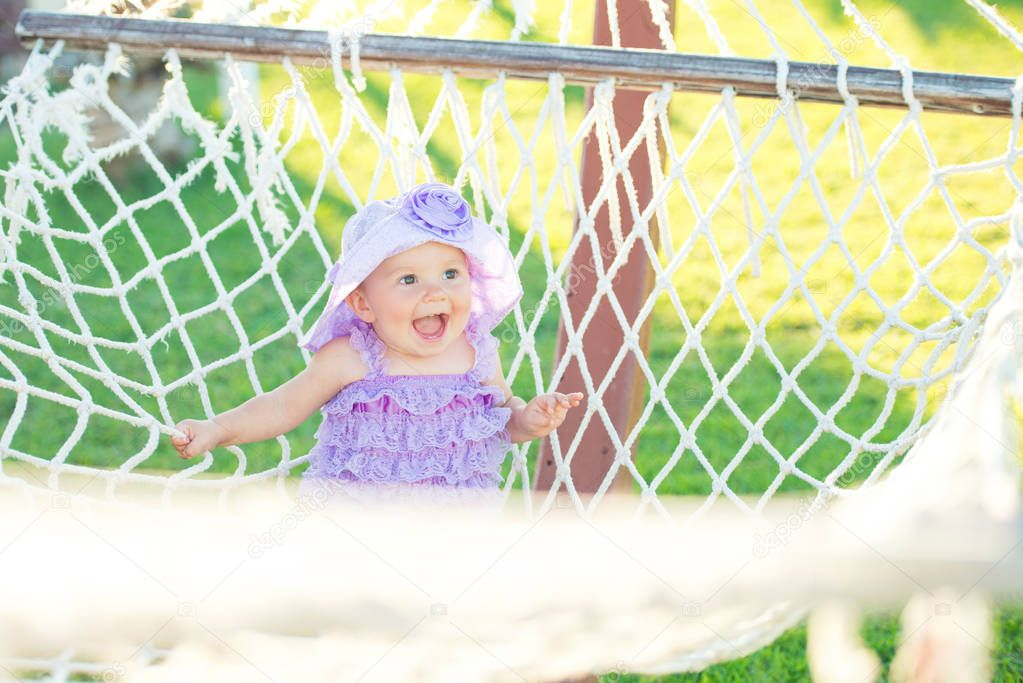 Portrait of happy girl on vacation. Against a background of hammocks, a little girl is sitting in a purple plait