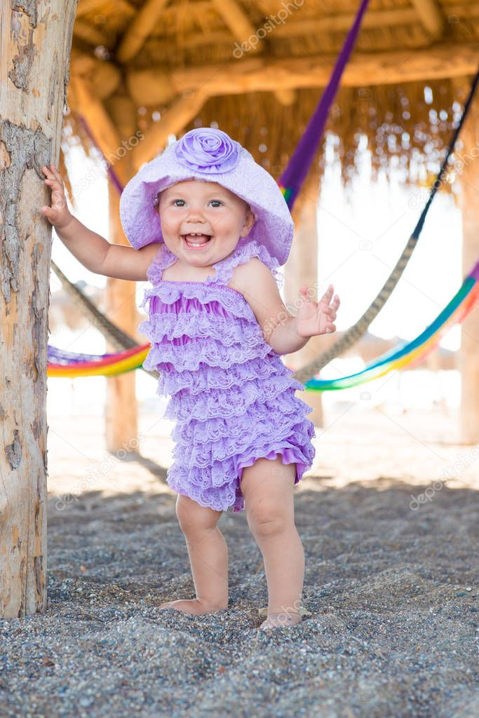 Portrait of happy girl on vacation. Against a background of hammocks, a little girl in a purple plait