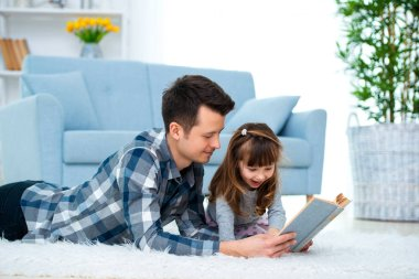 Cute little girl listening to dad reading fairy tale lying on warm floor together, caring father holding book , family hobbies activities at home.