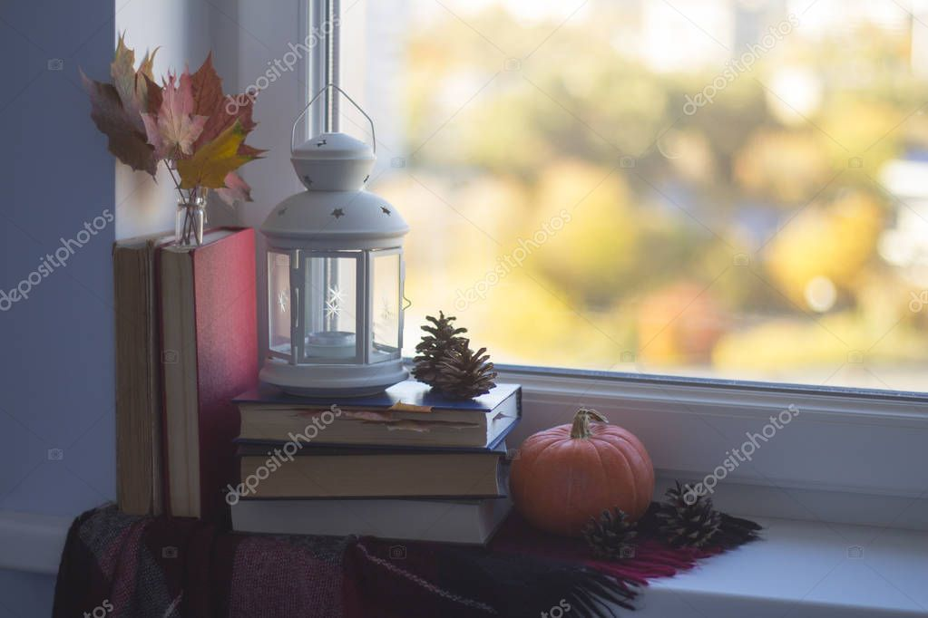 Autumn still life on a window sill. Pile of books, plaid, pumpkin, lamp, leaves and cones